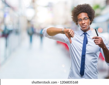 Afro american man holding credit card over isolated background with angry face, negative sign showing dislike with thumbs down, rejection concept