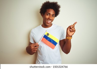 Afro american man holding Venezuela Venezuelan flag standing over isolated white background very happy pointing with hand and finger to the side