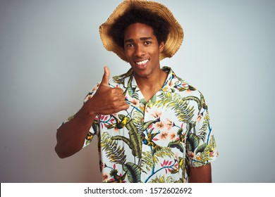Afro american man on vacation wearing summer shirt and hat over isolated white background doing happy thumbs up gesture with hand. Approving expression looking at the camera with showing success.