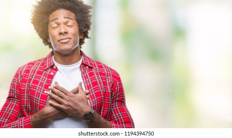 Afro american man over isolated background smiling with hands on chest with closed eyes and grateful gesture on face. Health concept.