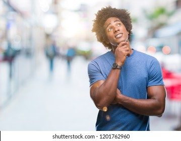 Afro american man over isolated background with hand on chin thinking about question, pensive expression. Smiling with thoughtful face. Doubt concept.