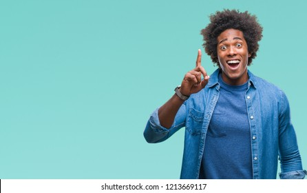 Afro american man over isolated background pointing finger up with successful idea. Exited and happy. Number one.