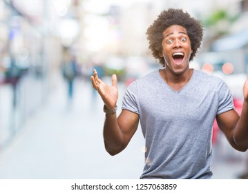 Afro american man over isolated background celebrating crazy and amazed for success with arms raised and open eyes screaming excited. Winner concept