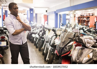 Afro american man is shopping and choosing new motobike in moto store. High quality photo