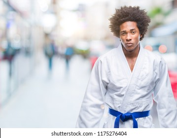 Afro american man wearing karate kimono over isolated background skeptic and nervous, frowning upset because of problem. Negative person.