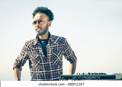 Afro american model artist ready to perform at dj console during spring break festival - Hipster funky disc jockey at summer beach party - Male trendy person with sunglasses at disco rave event
