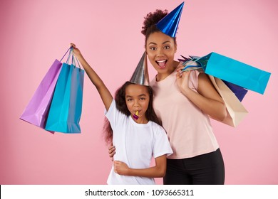 Afro American mother and daughter in holiday caps keep paper glossy bags. Shopping and consumerism concept. Isolated on pink background. Studio portrait.