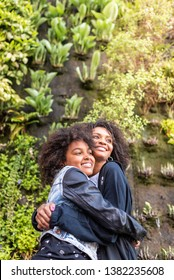 Afro American Mother and Daughter Hugging to Each Other Outdoors . Latin American Mother Having Fun with her Daughter . Separated Mother Hugging her Daughter. Family Concept.