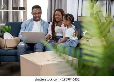 Afro american parents sitting on couch with their cute daughter and using laptop. Young family taking break during removing to new flat.