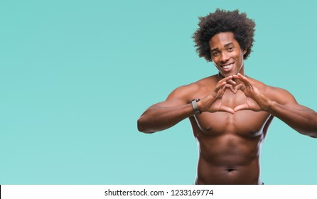 Afro american shirtless man showing nude body over isolated background smiling in love showing heart symbol and shape with hands. Romantic concept.