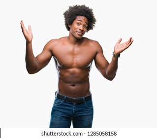 Afro american shirtless man showing nude body over isolated background clueless and confused expression with arms and hands raised. Doubt concept.