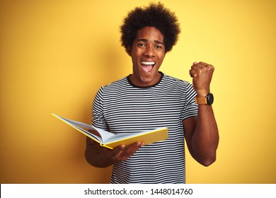 Afro american student man reading book standing over isolated yellow background screaming proud and celebrating victory and success very excited, cheering emotion
