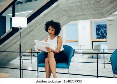 Afro-amerikanischer erfolgreicher Unternehmer, der in formaler Kleidung verkleidet ist, liest Finanzberichte aus Papierdokumenten, Geschäftsfrau überprüft Buchführung sitzend im Bürovorsitzenden Unternehmen