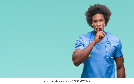 Afro american surgeon doctor man over isolated background asking to be quiet with finger on lips. Silence and secret concept.