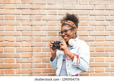 Afro American Teenage Girl Using a Film Camera Outdoors. Afro Girl Taking a Picture with a Vintage Camera. Youth Concept.