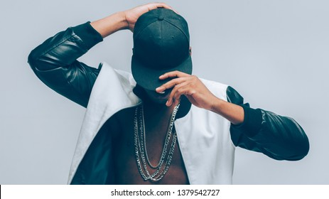 Afro american urban guy. Rapper posing in cap and leather jacket on naked torso. Head tilted down. Rap culture lifestyle.