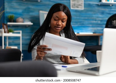 Afro american woman analyzing financial graph document remote working at marketing presentatrion in living room. Smart black student checking accounting infographics planning statistics at home - Shutterstock ID 2008508747