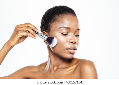Afro american woman applying makeup with brush isolated on a white background