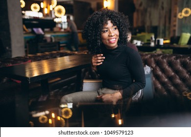 Afro american woman happy in a cafe