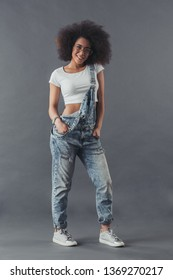 Afro American woman in jean overalls and eyeglasses is posing at camera and smiling, on a grey background, full-length