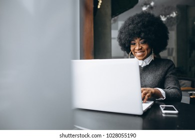 Afro american woman with laptop in a cafe