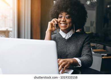 Afro american woman with laptop and phone in a cafe