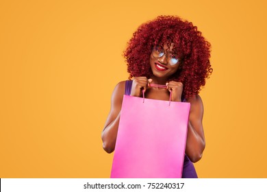 Afro american woman at shopping holding pink bag isolated on orange background on black friday holiday. Copy space for sale ads. Double Eleven Shopping Festival .