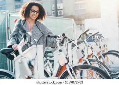 Afro american woman taking a bicycle in a bike rental platform