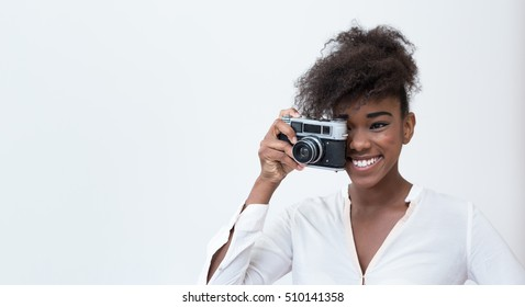 Afro american woman taking a picture with a  vintage camera