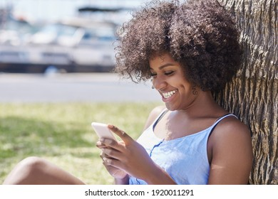 Afro american woman using mobile laughing under tree
