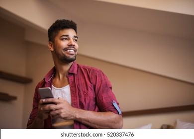 Afro American young man looking aside while typing message on his smartphone.