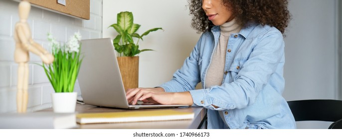 Afro american young woman student freelancer distance worker using laptop elearning online course work study from home office typing on computer at desk. Horizontal photo banner for website design.