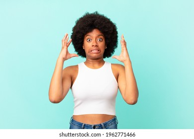 afro black woman screaming with hands up in the air, feeling furious, frustrated, stressed and upset