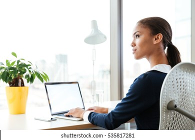 Afro Business woman in dress sitting by the table near the window with laptop and looking aside in office