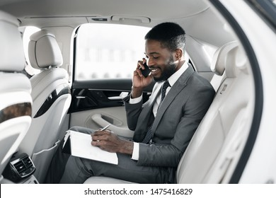 Afro businessman arranging his affairs with notepad in the car, talking on phone
