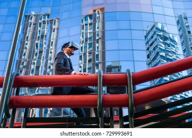 afro businessman playing virtual reality simulation, business buildings on the background
