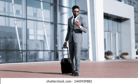 Afro Businessman Using Phone, Arriving at Airport and Waiting for Taxi Outdoors