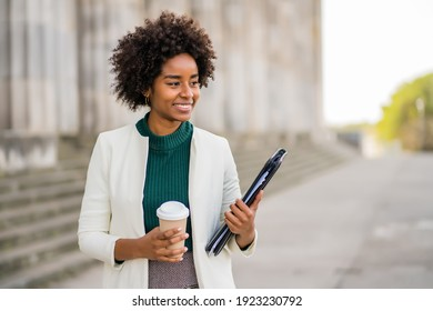 Afro businesswoman walking outdoors on the street.