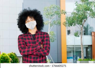 Afro College Student sieht zuversichtlich mit gefalteten Armen, während sie eine Maske tragen und auf dem Universitätsgelände stehen