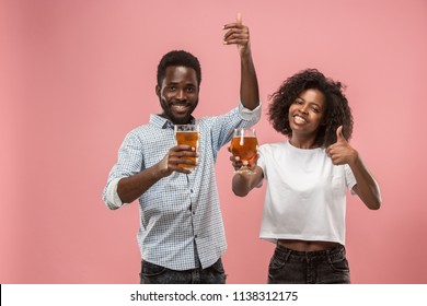 The afro couple or happy young people laughing and drinking beer at studio over pink. Human facial emotions concept.