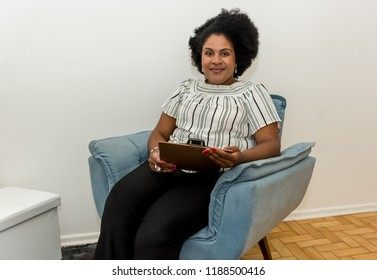 Afro descendant woman in office fiddling with papers and notebook psychologist and her patient