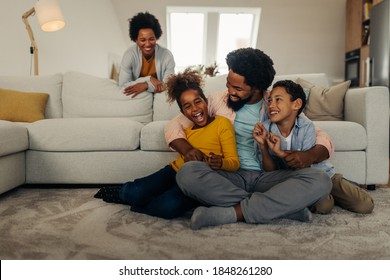 Afro father and children having fun at home