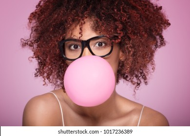 Afro girl blowing a bubble gum balloon over pink background, looking at camera.