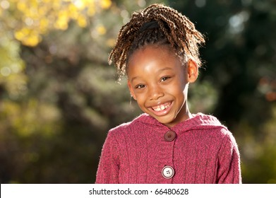 Afro girl enjoying nice sunny day in a park.