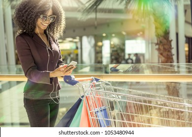 afro girl at shopping mall carrying shopping bags and pushing cart