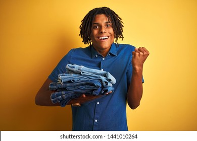 Afro man with dreadlocks holding stack of folded jeans over isolated yellow background screaming proud and celebrating victory and success very excited, cheering emotion