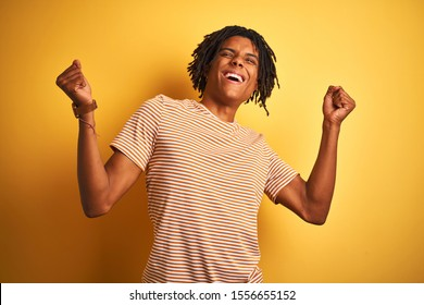 Afro man with dreadlocks wearing striped t-shirt standing over isolated yellow background celebrating surprised and amazed for success with arms raised and eyes closed. Winner concept.