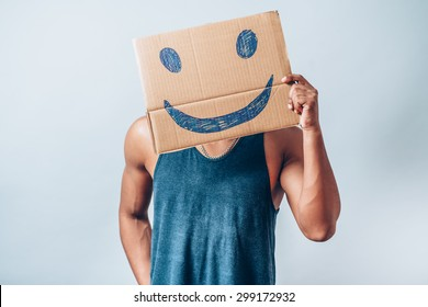 Afro man holding a cardboard with a smiley. On a gray background.