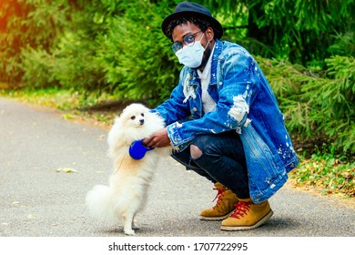 afro man in mask hugging his fluffy spitz in park