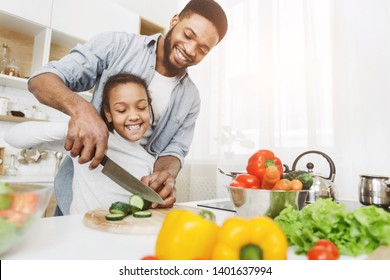 Afro man teaching his little daughter to cut vegetables, cooking salad. Family cooking school concept, copy space
